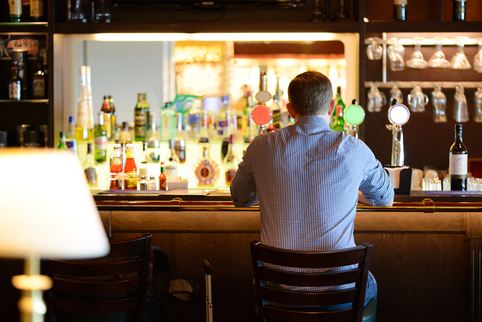 Lonely man in shirt sitting at bar desk